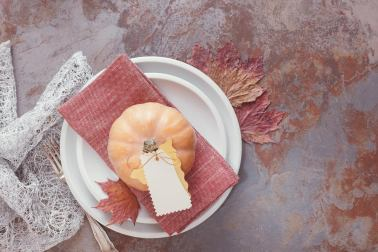 Fall table with pumpkins. White plates decorated with pumpkin, autumn leaves and placard